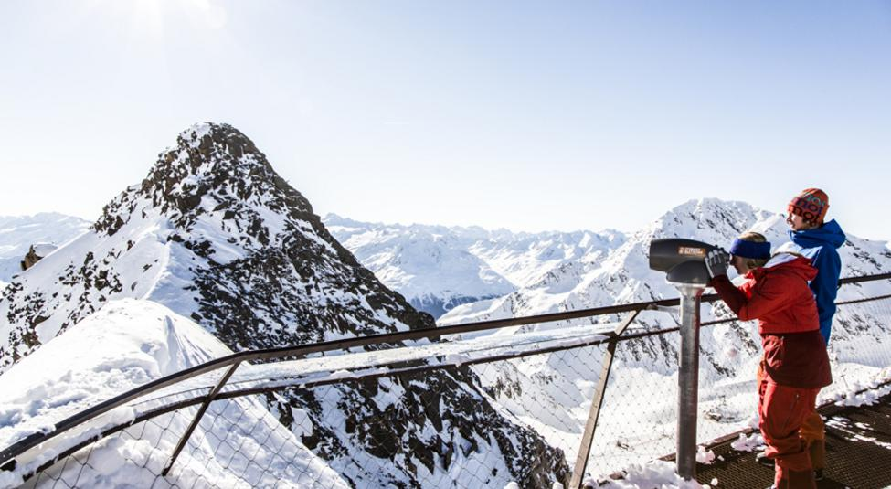 Woman looking through a telescope at the Stubai Glacier viewing platform