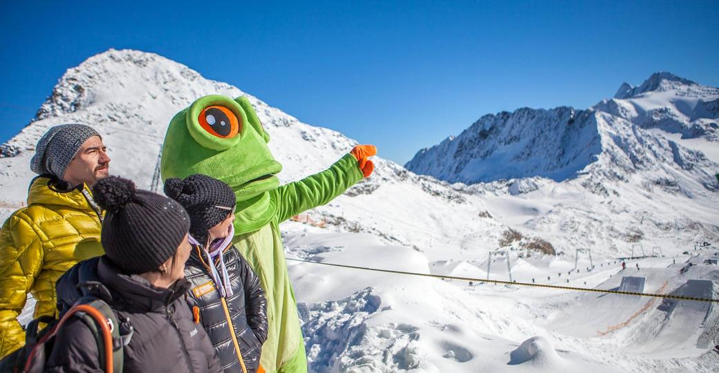 Frog mascot explains three people the mountains