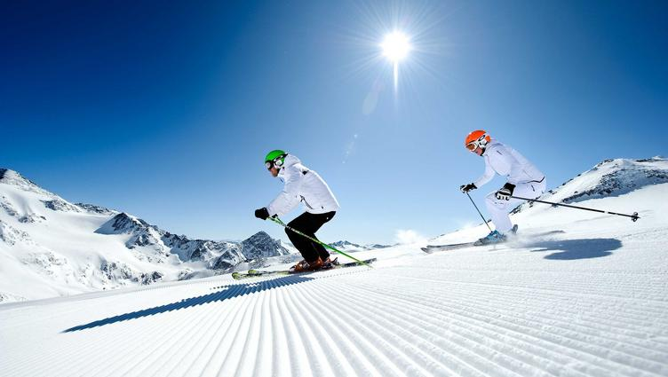 Two skiers on a piste