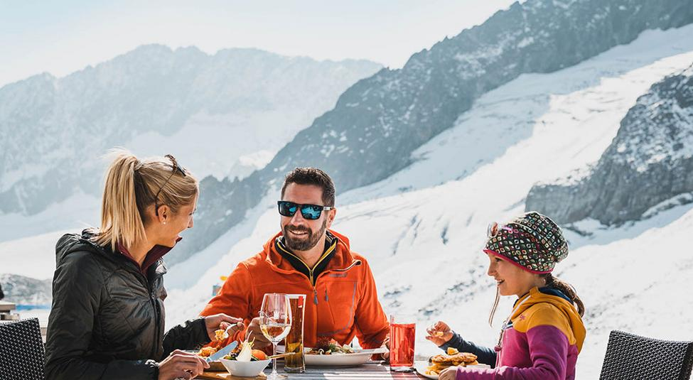 Family eating at a dining table on the Stubai Glacier in the summer