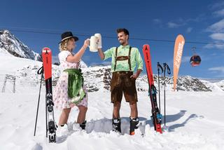 Two skiers drinking beer in the snow