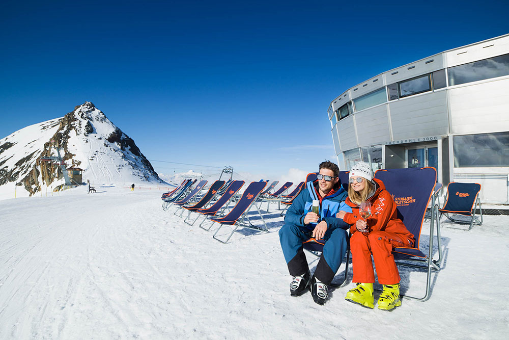Two skiers having an aperitivo while sitting in deck-chairs in front of the Jochdohle restaurant